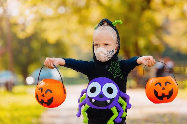 Un bambino nel giorno di happy halloween pesa i dolci raccolti, indossa una maschera protettiva decorata