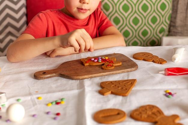 Un bambino decora il pan di zenzero di natale con caramelle colorate