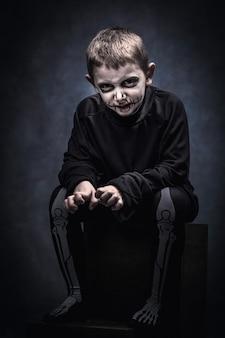 Bambino travestito da scheletro per evento di halloween, girato in studio.