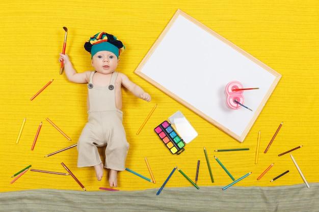 Bambino disegnare con matite colorate e pennarelli su carta sul pavimento