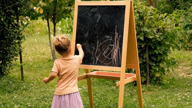 Bambino che disegna con il gesso alla lavagna