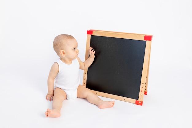 Un bambino disegna su una lavagna con il gesso su uno sviluppo bianco e precoce, fino a un anno,