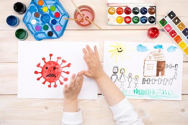 Un bambino disegna un coronovirus e la sua famiglia su un pezzo di carta