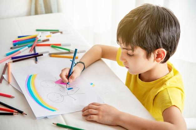 Il bambino disegna la sua famiglia su un pezzo di carta con matite colorate. concetto di psicologia infantile.