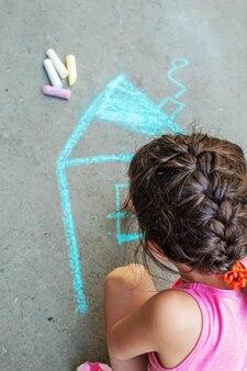 Il bambino disegna la casa con il gesso sull'asfalto. messa a fuoco selettiva. disegno.