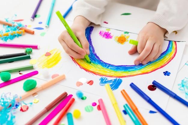 Il bambino disegna un arcobaleno con pennarelli