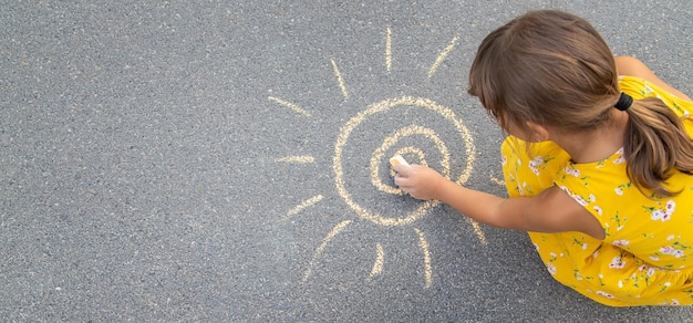 Il bambino disegna il sole sull'asfalto. messa a fuoco selettiva.