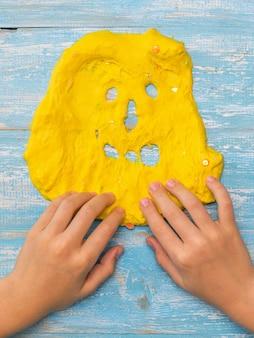 Il bambino disegna i denti su una faccia di melma gialla su un tavolo di legno. giocattolo antistress. giocattolo per lo sviluppo delle capacità motorie della mano.