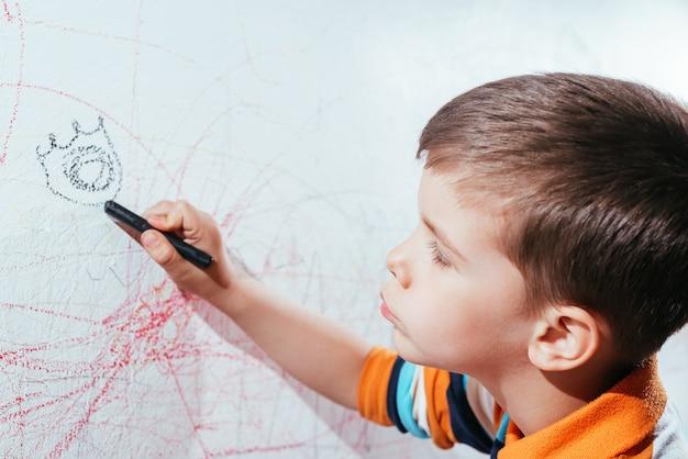 Il bambino disegna sul muro con il gesso colorato. il ragazzo è impegnato nella creatività a casa