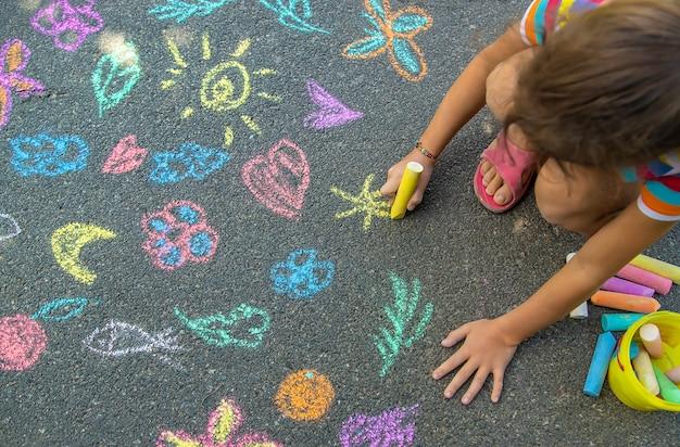 Il bambino disegna con il gesso sull'asfalto