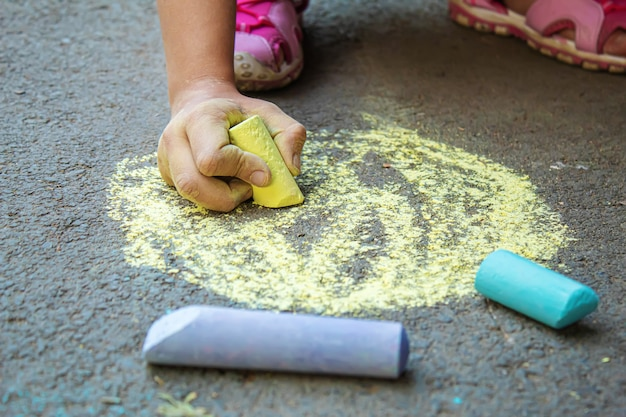 Il bambino disegna con il gesso sul marciapiede. messa a fuoco selettiva.arti