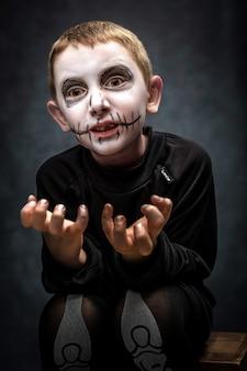 Bambino vestito come scheletro in posa spaventosa. costume di halloween, girato in studio