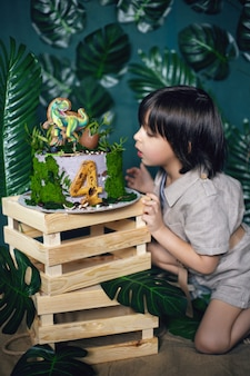 Bambino vestito nello stile di un cacciatore di tesori della giungla con un cappello e una torta di dinosauro