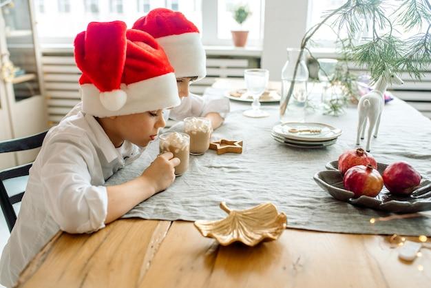 Bambino bere cioccolata calda di natale a casa. famiglia con bambini festeggia le vacanze invernali.