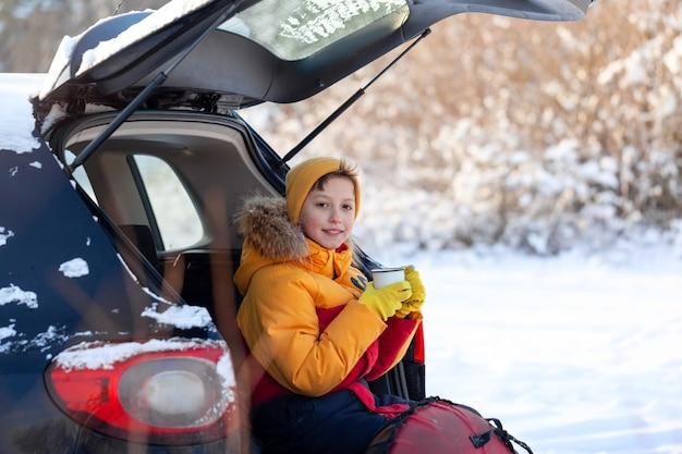 Bambino che beve cioccolata calda o cacao seduto in macchina nera al giorno d'inverno nevoso. staycation, viaggi, turismo in inverno.