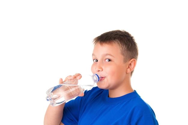 Il bambino beve acqua pulita dalla bottiglia isolata su sfondo biancoil ragazzo indossa una maglietta blu