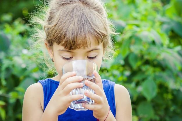 Il bambino beve acqua pulita in estate. messa a fuoco selettiva.