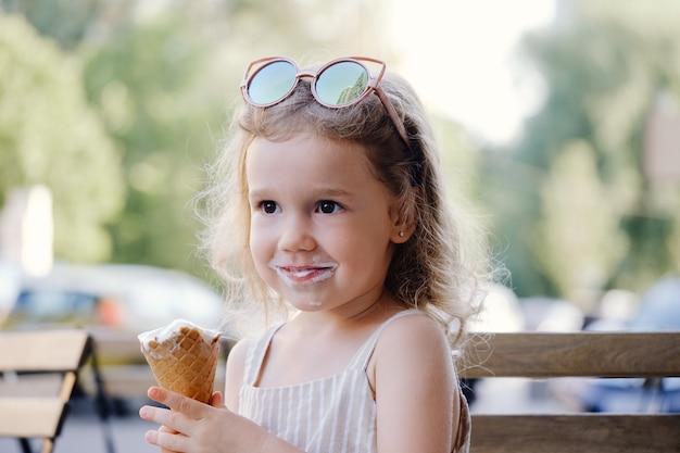 Bambino che mangia il gelato del cono fuori vicino al cibo estivo congelato del bar