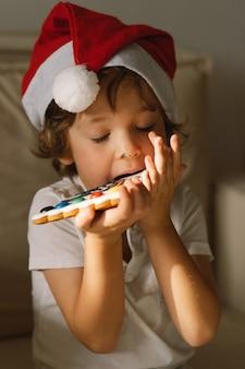 Un bambino che mangia i biscotti lustrati del pan di zenzero