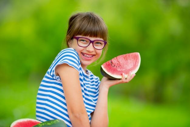 Bambino che mangia anguria ragazza pre-adolescente in giardino con in mano una fetta di anguria ragazza felice capretto ea...