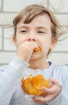 Il bambino mangia le patatine