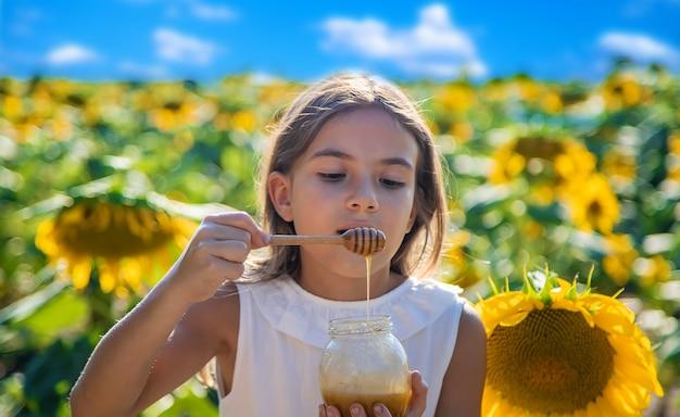 Il bambino mangia miele di fiori. messa a fuoco selettiva. natura.