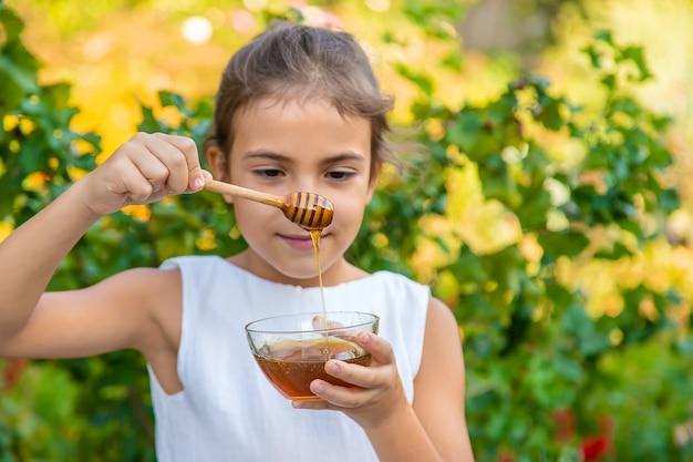 Il bambino mangia miele di fiori. messa a fuoco selettiva.