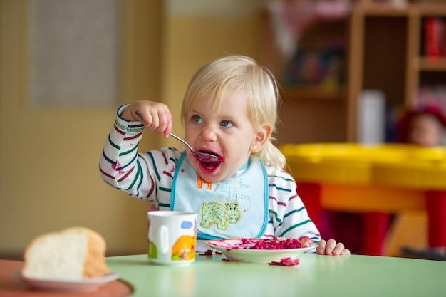 Il bambino mangia cibo sano all'asilo oa casa e si sporca