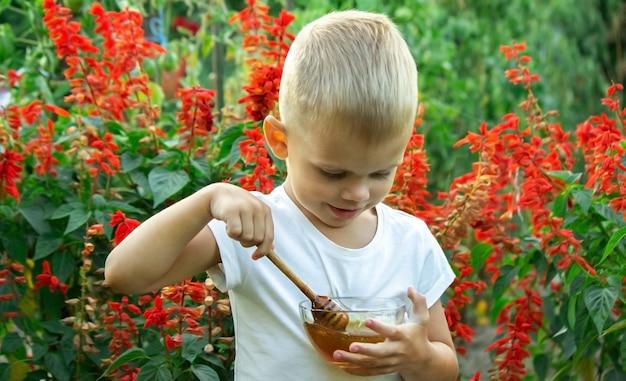 Il bambino mangia il miele in giardino. messa a fuoco selettiva