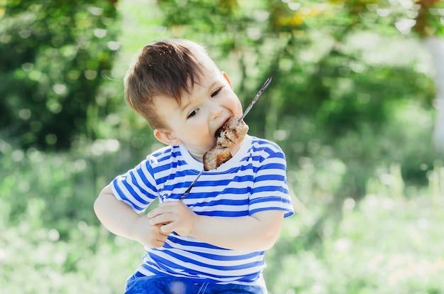 Un bambino mangia un kebab su uno spiedino, in un parco o in una natura forestale sfondo verde di alberi ed erba