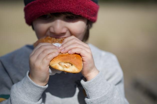 Il bambino mangia il panino all'aperto