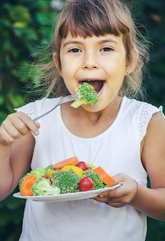 Il bambino mangia le verdure in estate. messa a fuoco selettiva. persone.