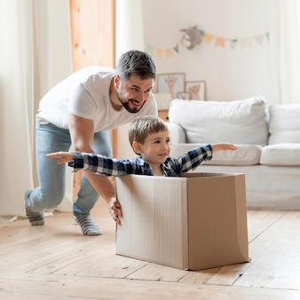Figlio e padre che giocano con una scatola in salotto