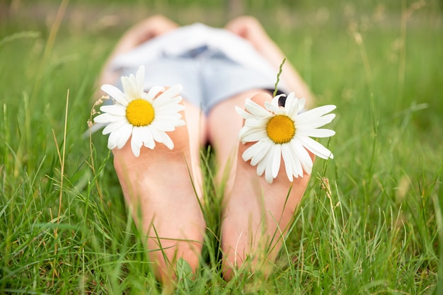 Piedi del bambino con il fiore della margherita. kid divertendosi alla natura primaverile. vacanza