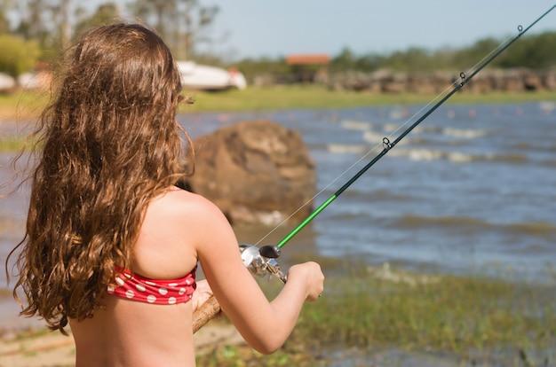 Pesca del bambino in stagno, lago.