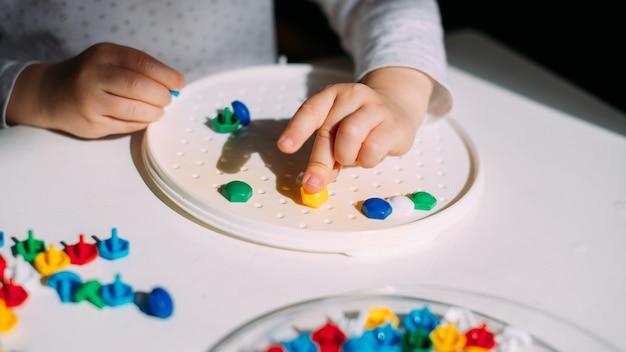 Il bambino piega il mosaico in una forma di plastica.