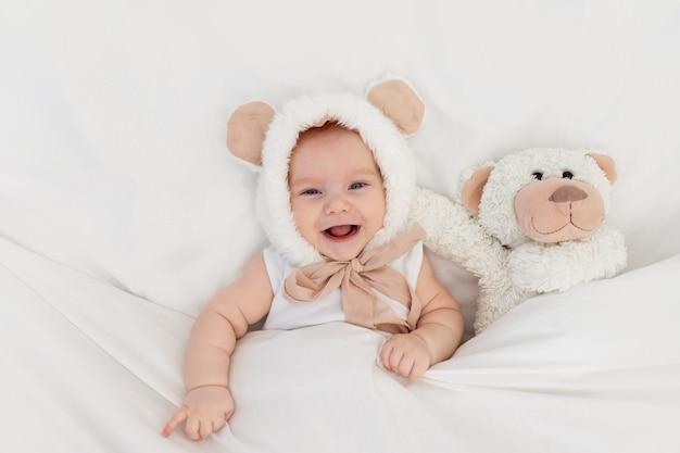 Un bambino con un buffo cappello con le orecchie e un orsacchiotto sotto la coperta. tessili e biancheria da letto per bambini. un neonato si è svegliato o sta andando a letto