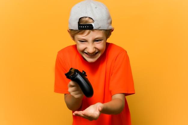 Un bambino giocatore tiene in mano un gamepad e mostra le emozioni premendo i pulsanti