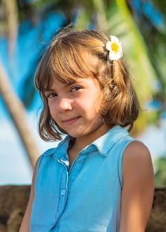 Ragazza del bambino sullo sfondo di palme e oceano. messa a fuoco selettiva.