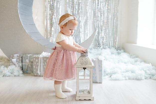 Bambina in un bellissimo vestito che tiene in mano una torcia vicino a decorazioni e regali di natale, vacanze invernali di capodanno