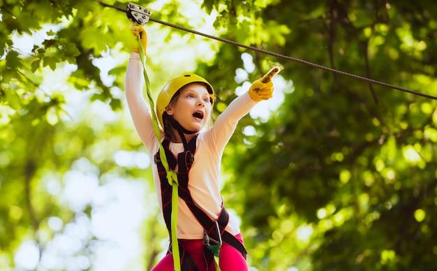 Ragazza del bambino arrampicata e divertimento nel parco avventura