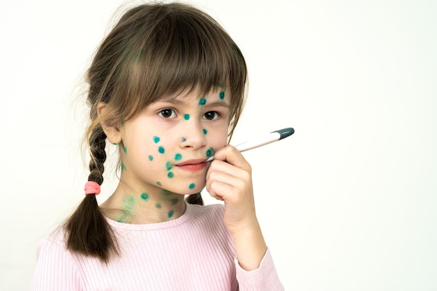 Ragazza del bambino ricoperta di eruzioni cutanee verdi sul viso malato di virus della varicella, del morbillo o della rosolia che tiene un termometro medico in bocca con febbre alta.