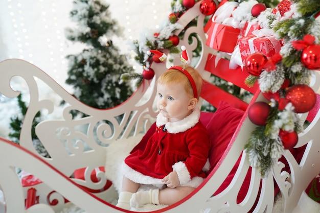 Bambina vestita da babbo natale vicino all'albero di natale e ai regali, vacanze invernali di capodanno