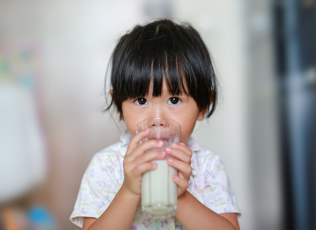 Ragazza del bambino che beve latte dal vetro