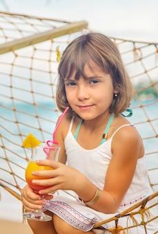 La ragazza del bambino beve il cocktail sulla spiaggia