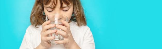 La ragazza del bambino beve l'acqua da un bicchiere. messa a fuoco selettiva.