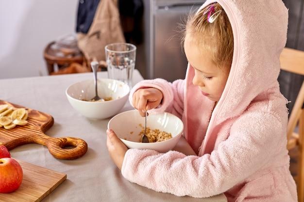 Ragazza del bambino che mangia colazione da solo in cucina, si siede mangiando un cucchiaio, indossando abiti domestici