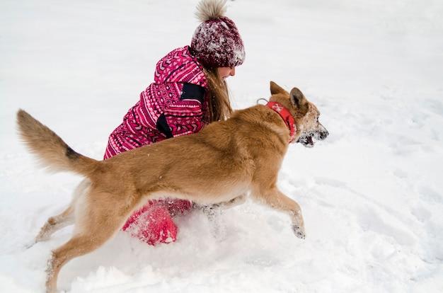 La ragazza del bambino ed il cane dorato dello sheperd giocano in neve all'aperto