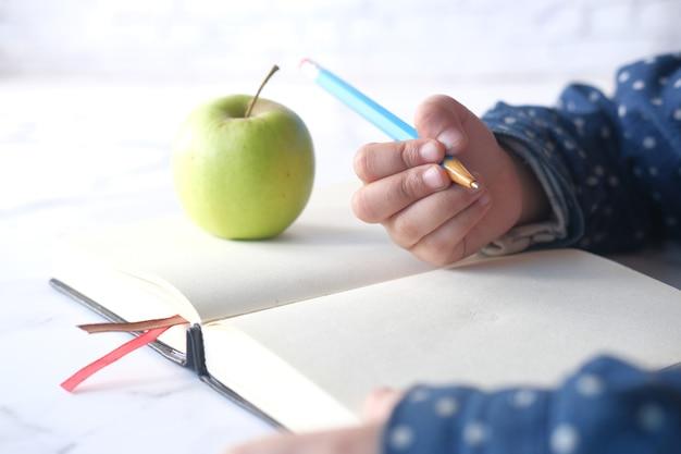 Scrittura della mano della ragazza del bambino sul blocco note con la mela fresca verde sul tavolo