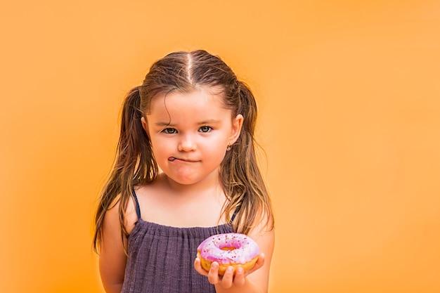 Holdind ragazza bambino sulla mano una ciambella rosa
